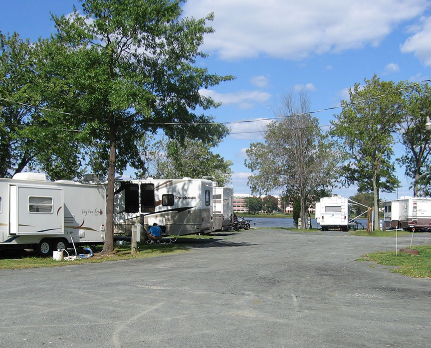 Various RVs are parked at their respective sites with a gravel road throughout; water is in the distance.