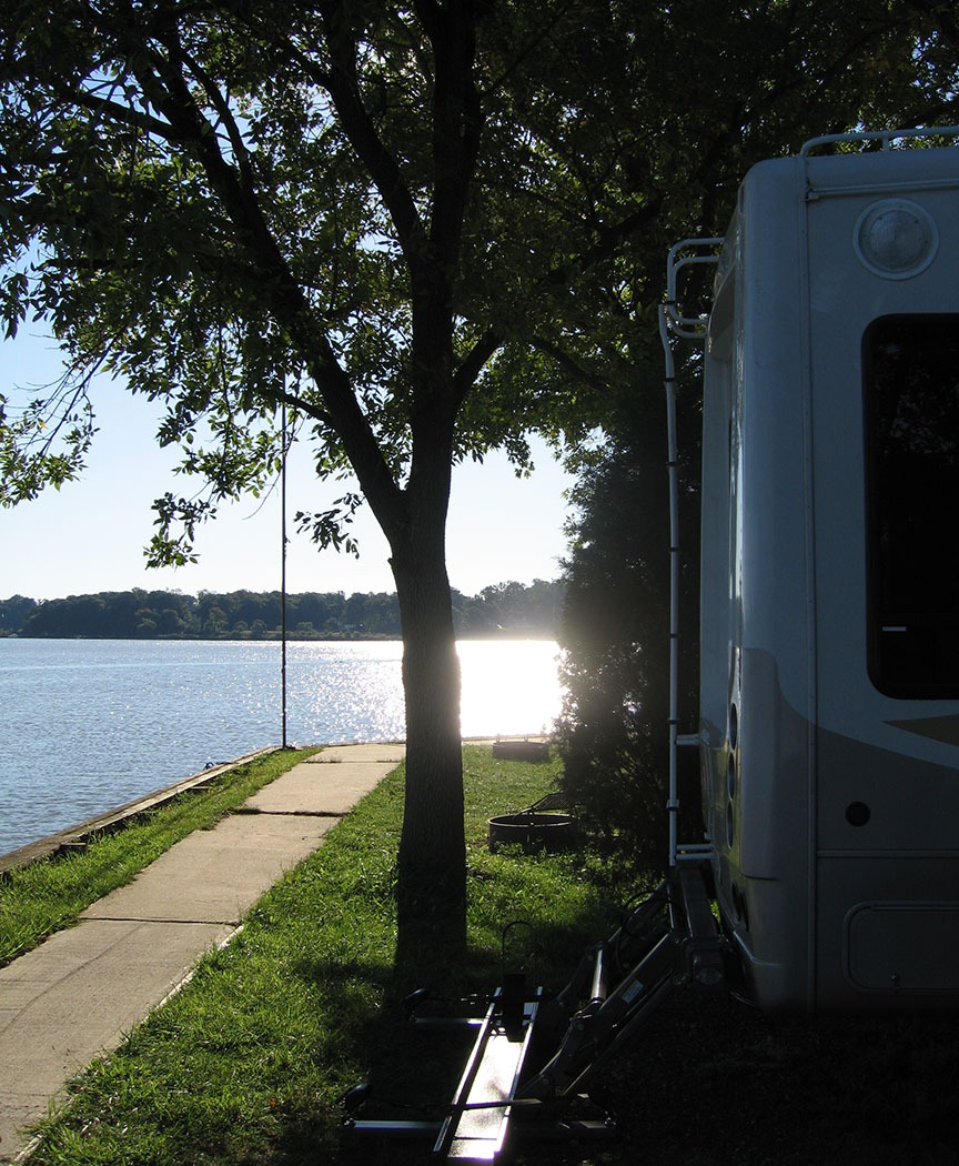 The water gleams with the sun; the back of the RV is close to the water