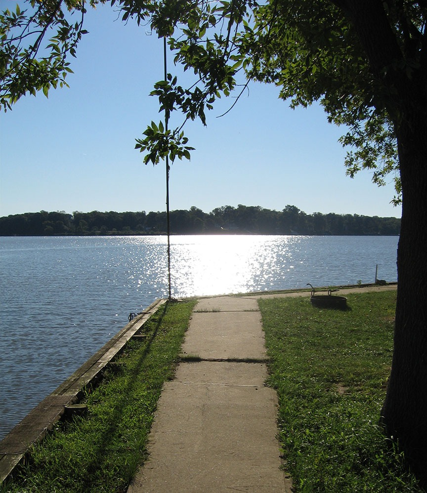 The sidewalk heads straight to the water; water gleams in the distance and stretches to the opposite shore where a treeline stands.