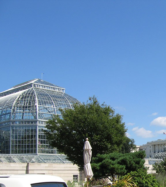 A glass dome of the Conservatory, part of the United States Botanic Garden, is backed by a bright blue sky.