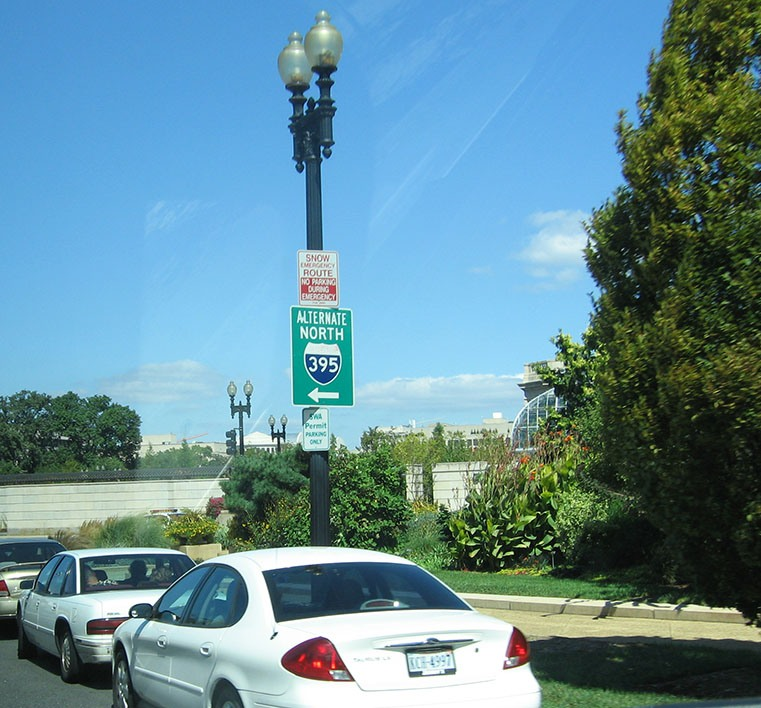"An alternate route sign reads ""Alternate North Interstate 395"" attached to a lamp post."