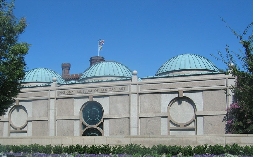 Three copper domes stand on top of a stone building; a bright blue sky stretches behind the building.