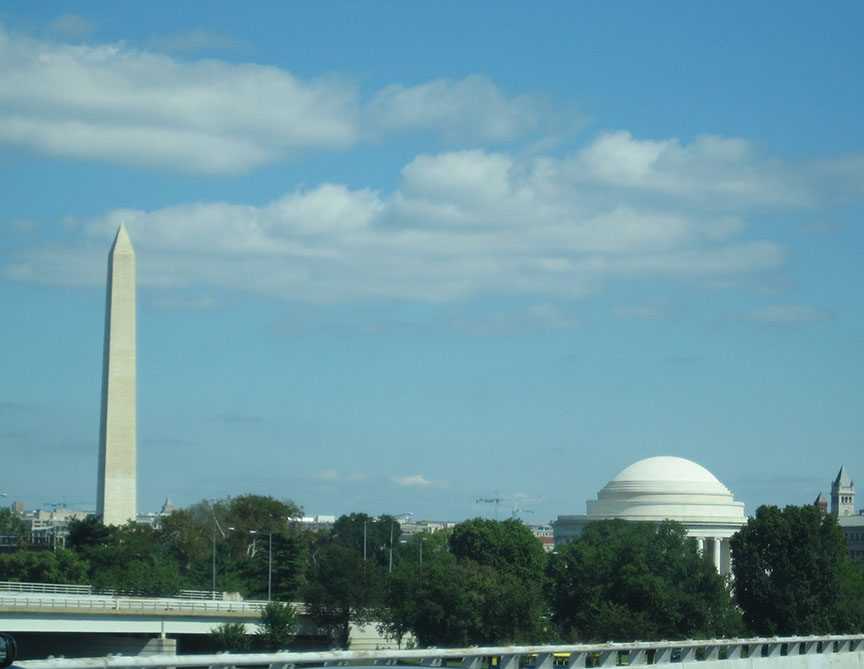 The Washington Monument stands tall in the left of the frame; the dome of Jefferson Memorial stands in the right of the frame.