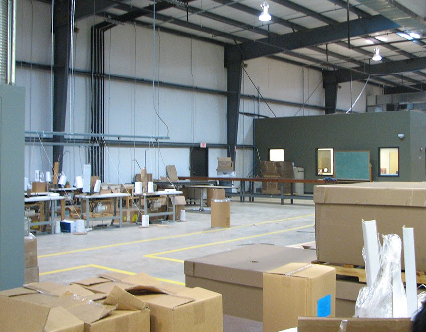 A warehouse with various boxes, machinery and areas for setup.