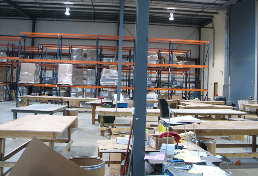Various work tables stand in one area of the warehouse.