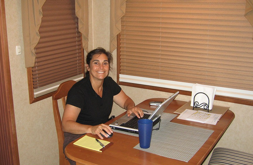 Lisa Gifford sits at a small table, working on a laptop, and grins to the camera.