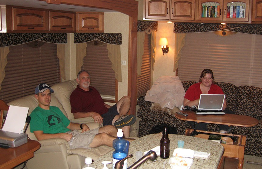 Shane Frost and Rick Gifford sit in the recliners on the RV, smiling to the camera; Shoshanah Bain sits on couch working on a laptop and smiling to the camera.