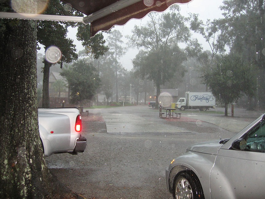 The back bumper of the truck peeks out from behind a tree trunk; the front fender of the convertible comes in from the left of the frame; rain downpours throughout the campground out of grey skies