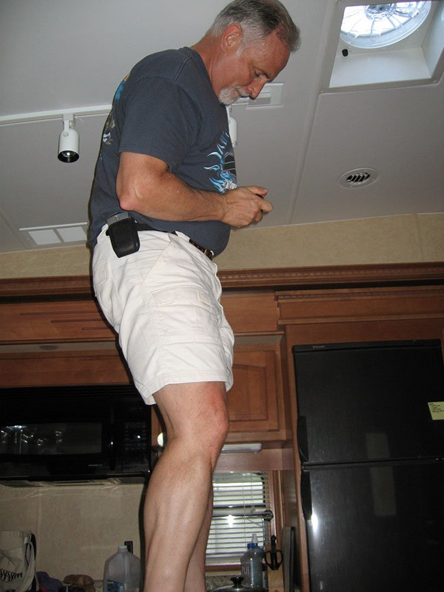 Rick Gifford stands on a table in the RV kitchen and works on replacing a light bulb.