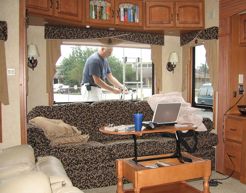 On the outside of the RV, Rick Gifford is working on the bike rack that is attached to the RV; inside the RV, a work station is setup in front of the couch and window.
