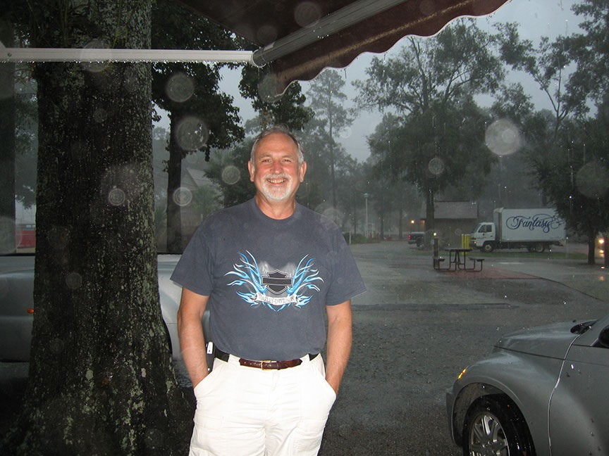 Rick Gifford stands under the awning of the RV, grinning to the camera; behind him, rain pours down out of dark grey skies.