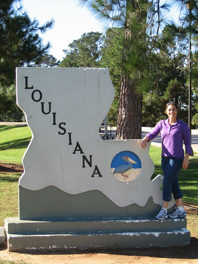 Lisa Gifford stands next to a sign that is shaped like the state of Louisiana; Louisiana is written on it