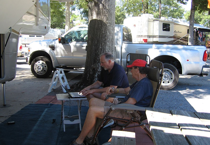 Rick Gifford sits in a chair outside at the RV site with another man next to him; both are focused on a laptop in front of them.