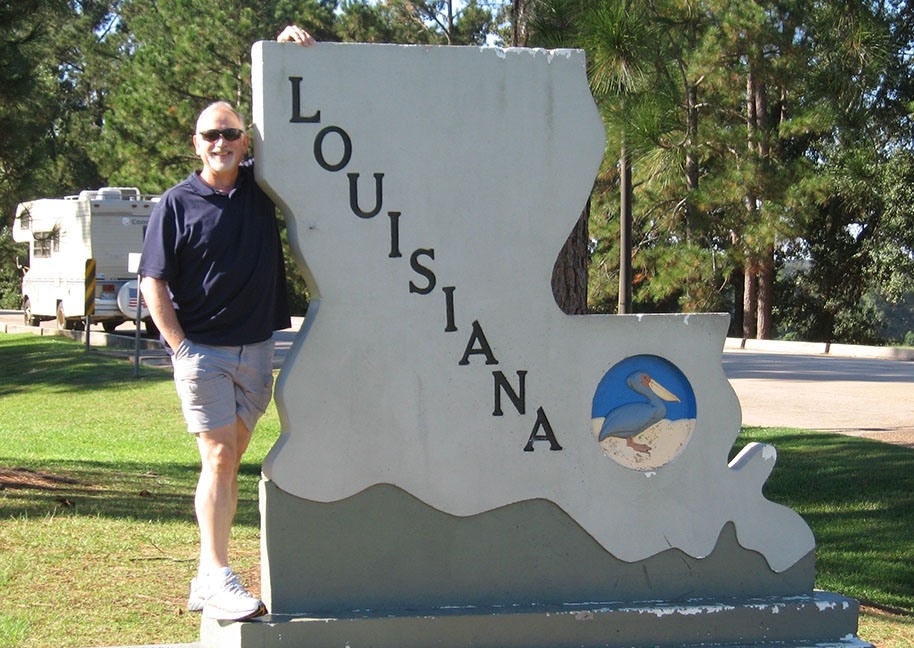 Rick Gifford stands next to a sign that is shaped like the state of Louisiana; Louisiana is written on it