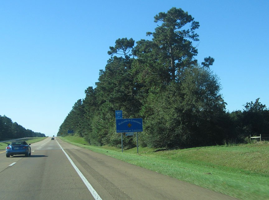 "A blue sign stands on the shoulder of the road and reads ""Welcome to Louisiana, Bienvenue en Louisane"""