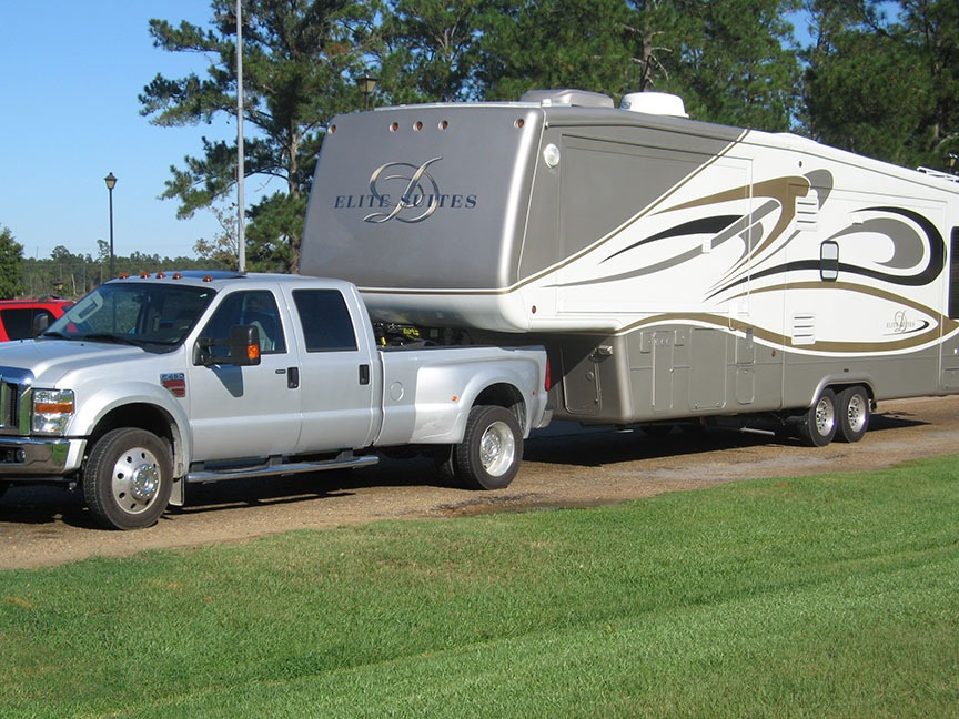 The silver truck pulling the fifth wheel is parked at a RV site.
