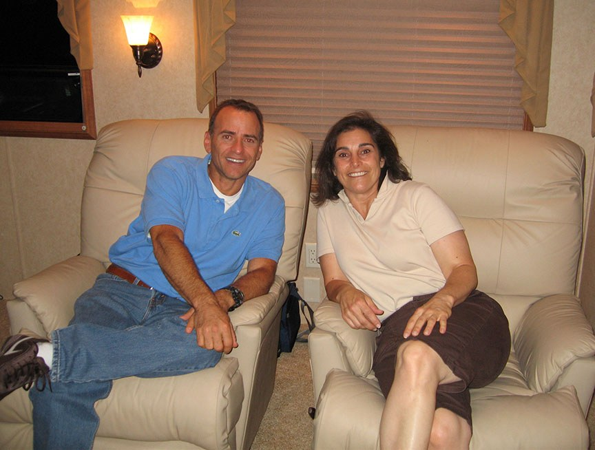 A man, Chuck, and Lisa, sit in recliners, both are smiling at the camera
