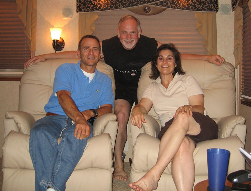 A man, Chuck, and Lisa sit in recliners; Rick kneels between the two recliners, arms draped over the back; all are smiling to the camera