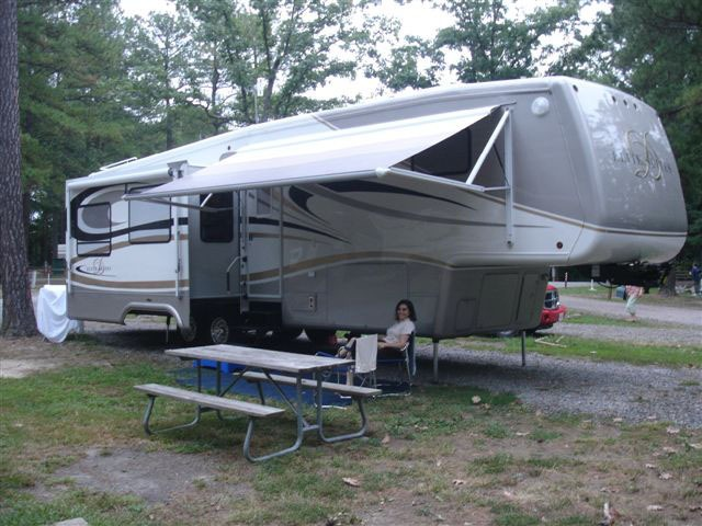 The RV stands alone - not hooked up to the truck - next to a picnic table, with it's awning open