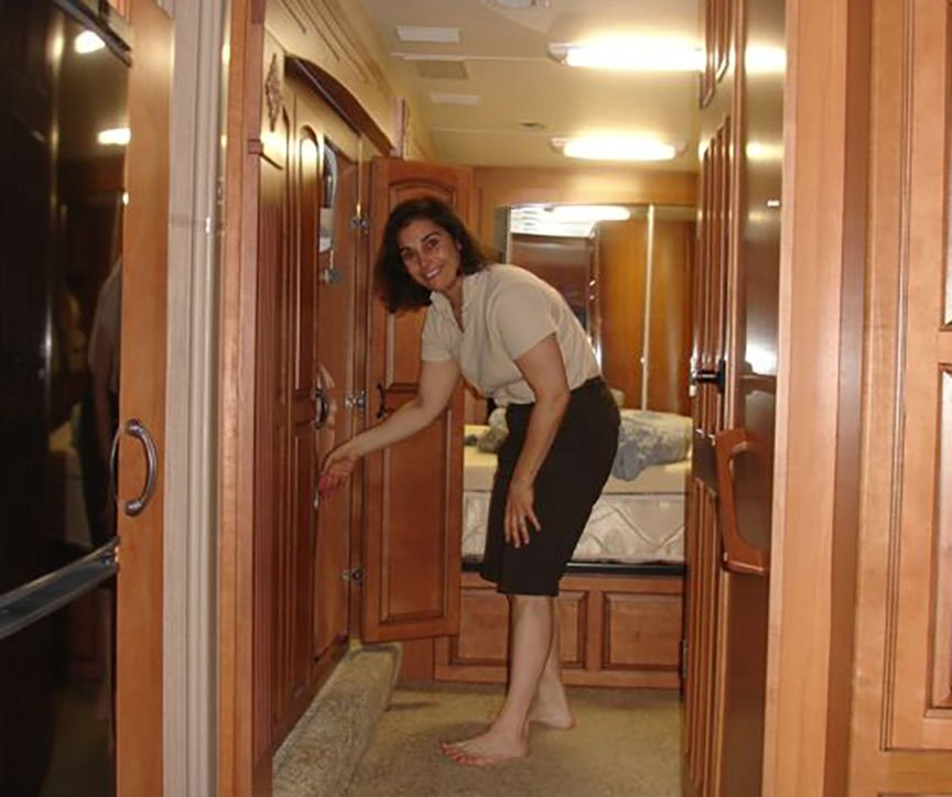 Lisa stands near an open cupboard in the hallway of the RV, smiling to the camera