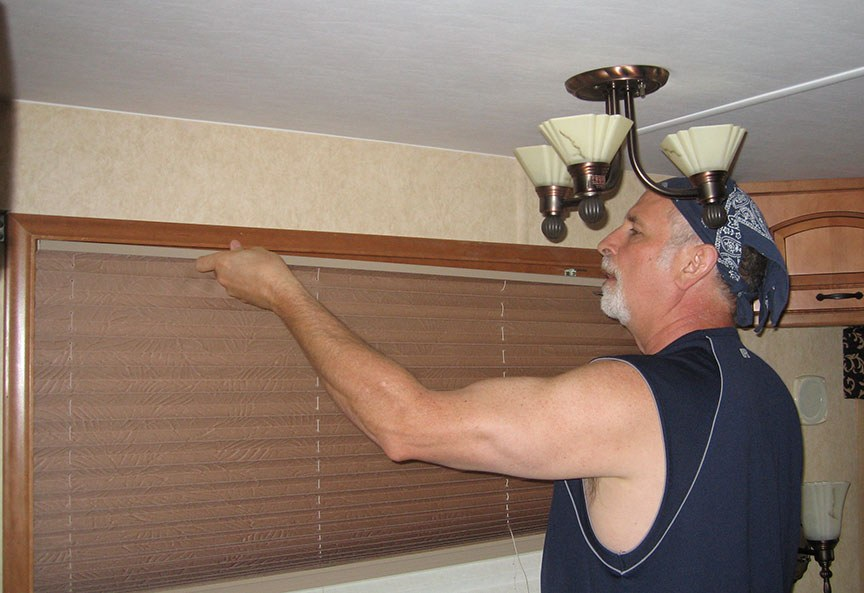 Rick stands fixing a part of the window blind inside the 5th Wheel