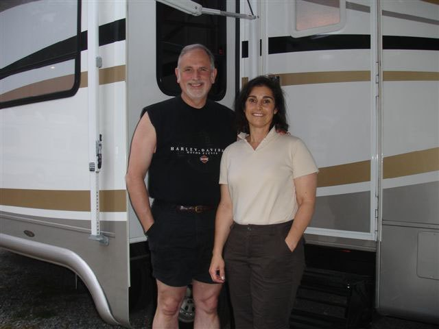 Rick and Lisa stand together, smiling, in front of the door to the RV