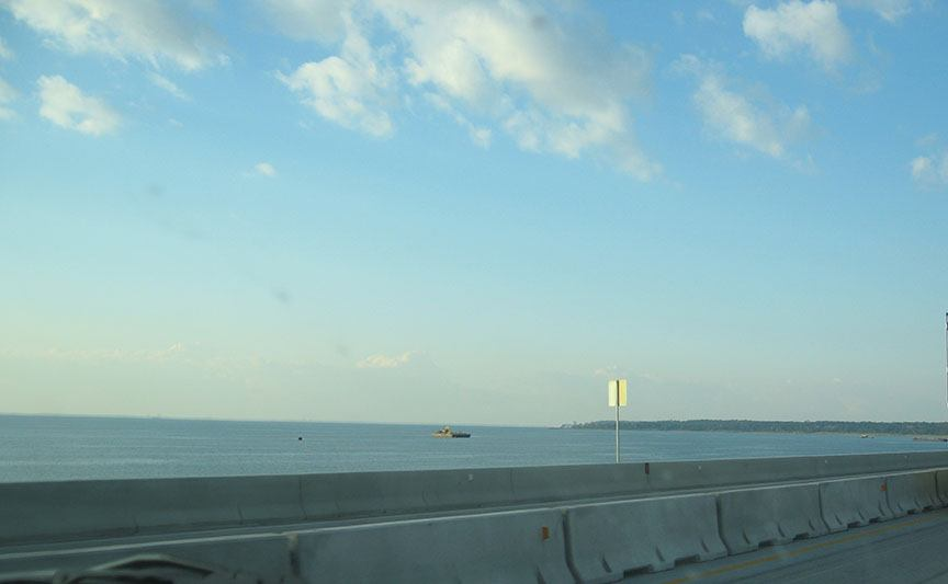 The roadway stretches along the bottom of the frame; beyond the road the Gulf of Mexico stretches out to meet the blue sky at the horizon.