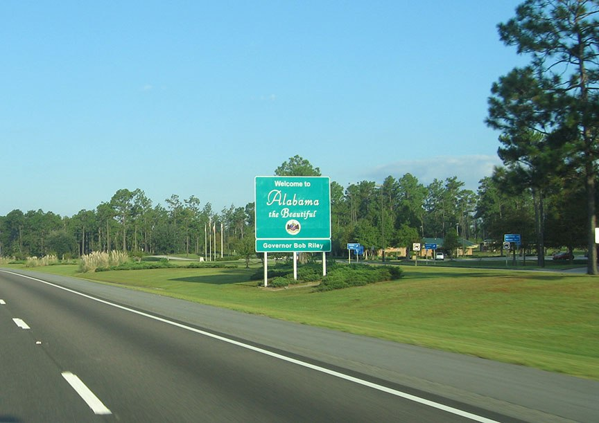 "A green sign stands in the grass on the right shoulder of the road and reads ""Welcome to Alabama the Beautiful, Governor Bob Riley"""