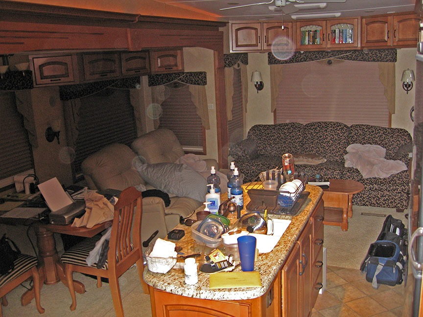 The interior of the RV is displayed and is very lived in; dishes fill the sink and clutter the counter, pillows and blankets are on the couches and sofa.