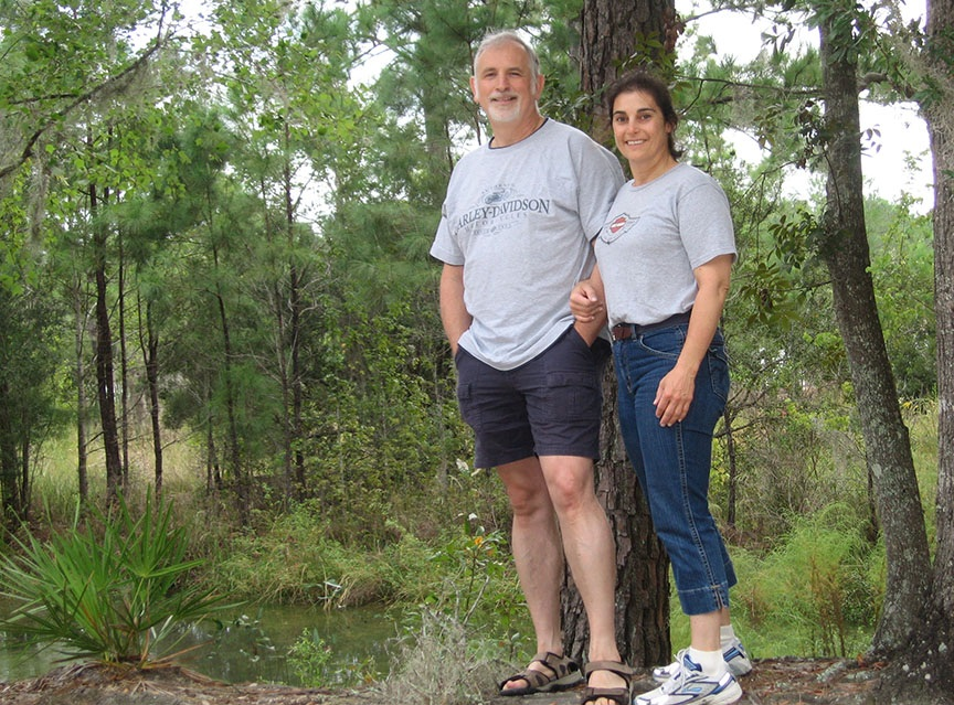 Lisa and Rick stand together in front of a small pond and trees hanging with moss; both are smiling to the camera.