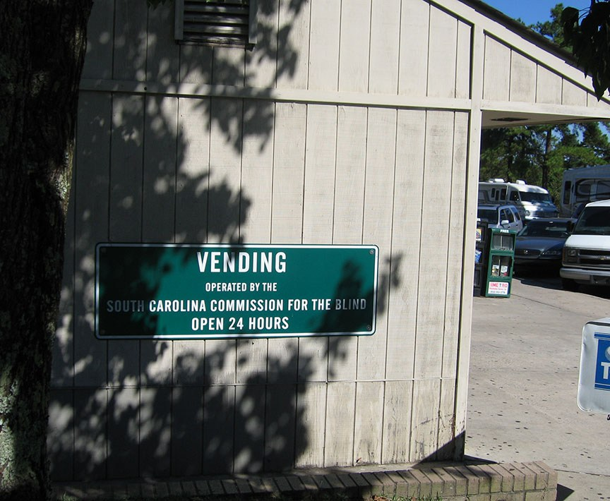 "A green sign on a white building reads ""Vending operated by the South Carolina Commission for the Blind Open 24 hours"""