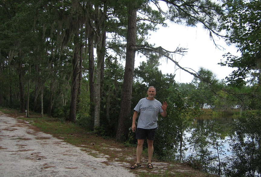 Rick stands on the edge of a gravel road, behind him is a body of still water and trees with hanging moss; Rick is smiling and waving to the camera.