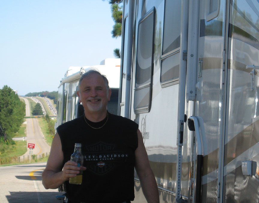 Rick Gifford stands next to the RV at a rest stop, a bottle of Sobe in his hand; behind him the highway stretches out with cars in both directions.