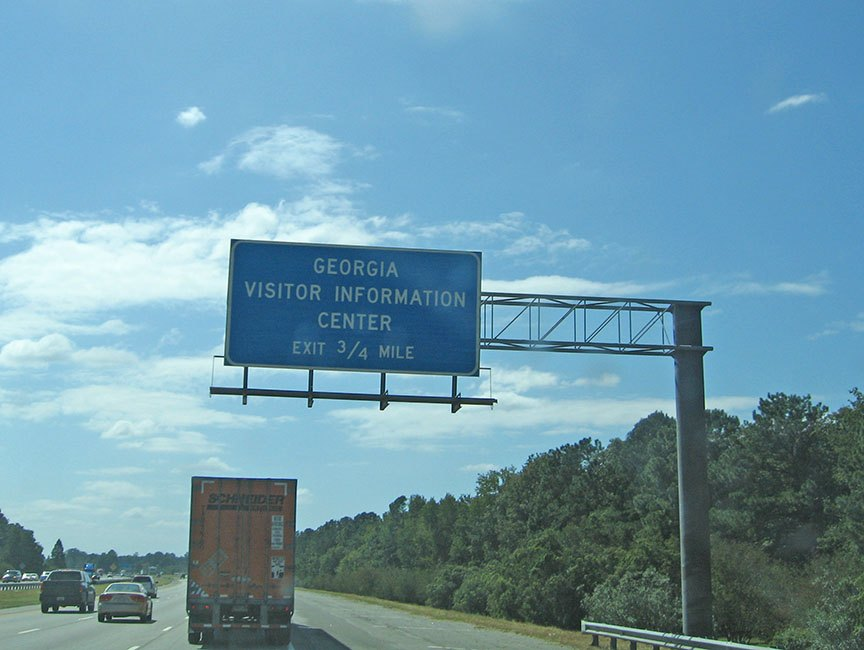 """A blue sign hangs over the highway and reads """"Georgia Visitor Information Center Exit 3/4 Mile"""""""
