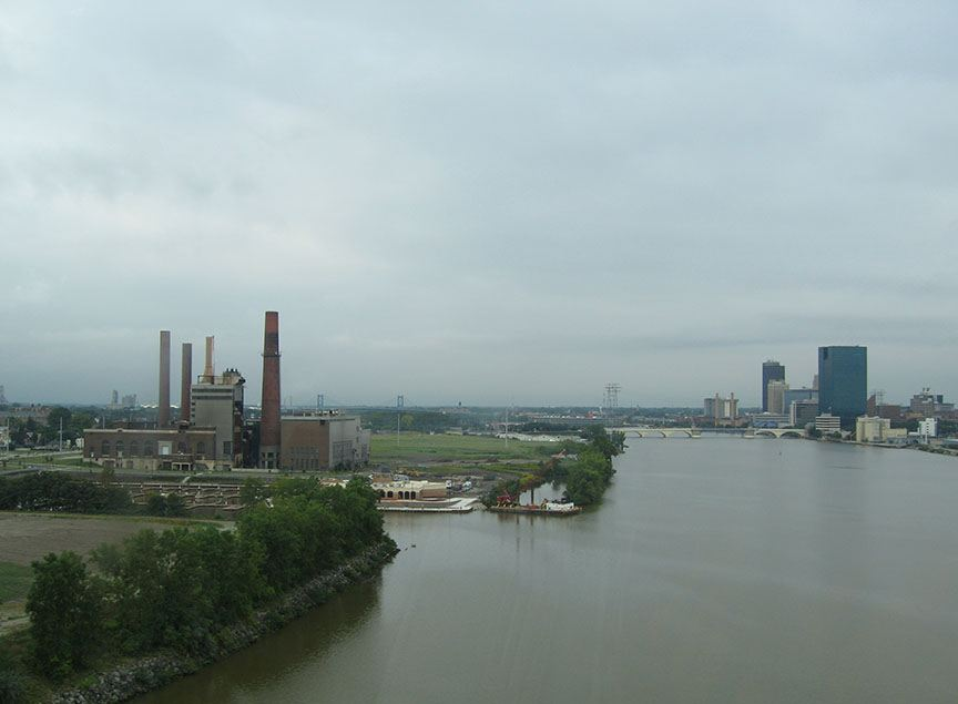 The Maumee River curves through the frame with industrial buildings on the left bank and city skyline on the right bank