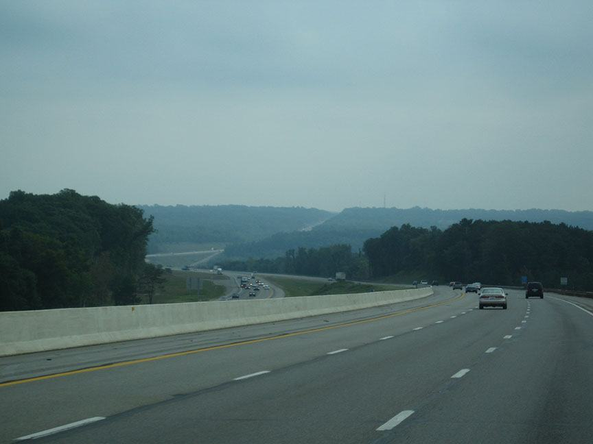 Lanes of the turnpike curve ahead of the truck, winding through low hills covered with trees