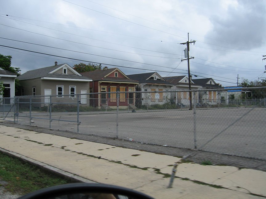 Six houses, still boarded up and mostly abandoned, line the street next to a vacant, fenced in lot