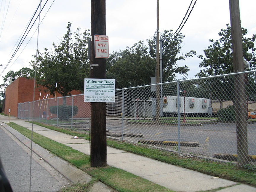 "A sign on a power pole reads ""Welcome Back Holy Cross Neighborhood Association""; behind it is a fenced in area that houses white FEMA trailers"