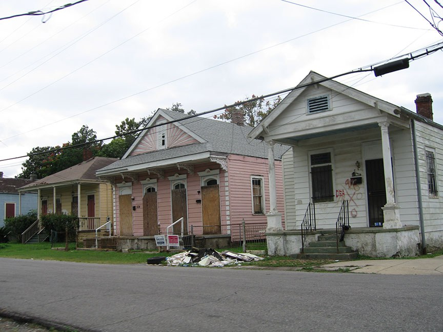 Three houses are boarded up, a pile of rubble sits in the front yard of one house; markings from the DEA are clearly painted on one house.
