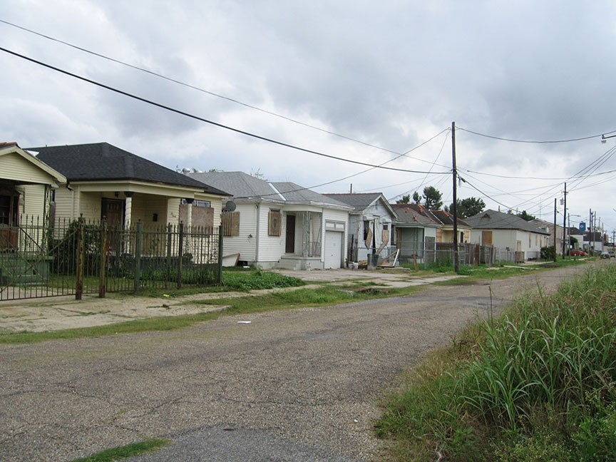 A row of devestated houses that have been boarded up line a street that is cracked and filled with pot holes