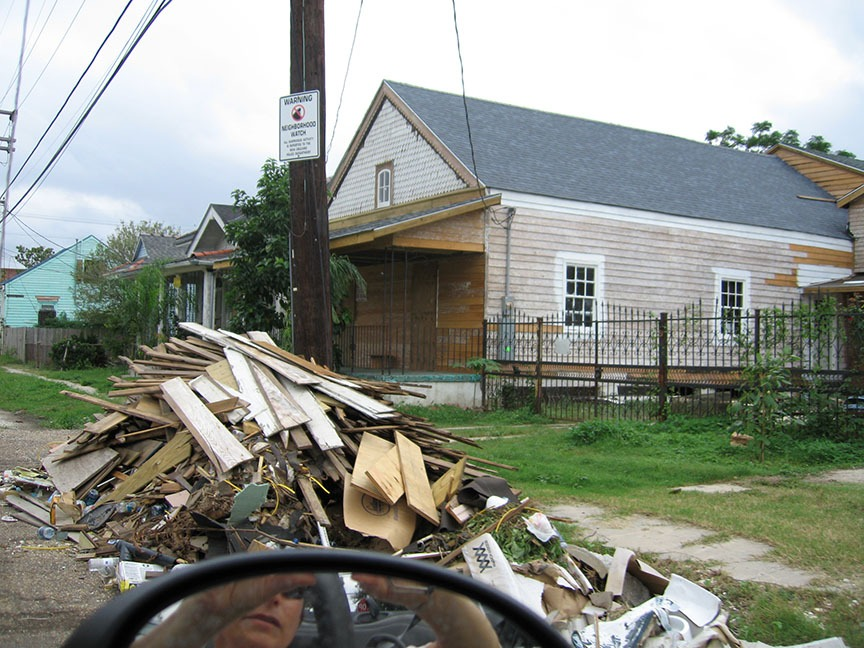 A large pile of debris stands in front of a house in the 9th Ward that has been boarded up and abandoned