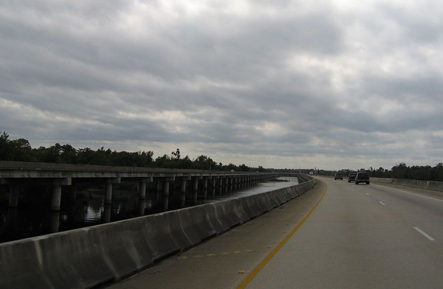 The highway stretches in both directions in front of the car; it is elevated above the waterways that flows underneath.