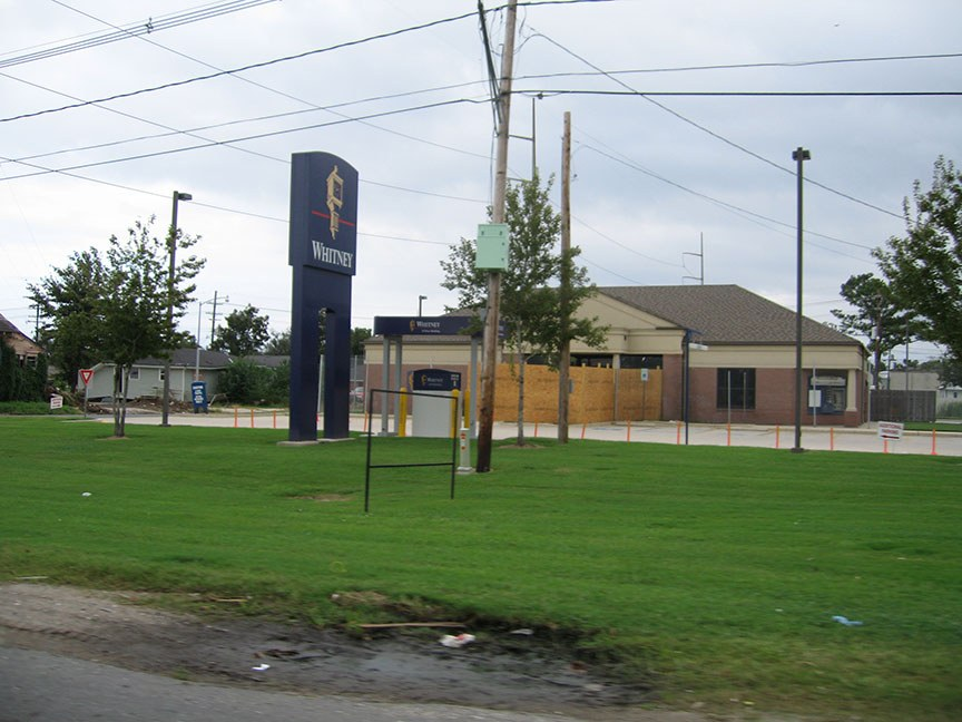 "A blue sign stands in front of a building, reads ""Whitney""; the building behind it is boarded up"