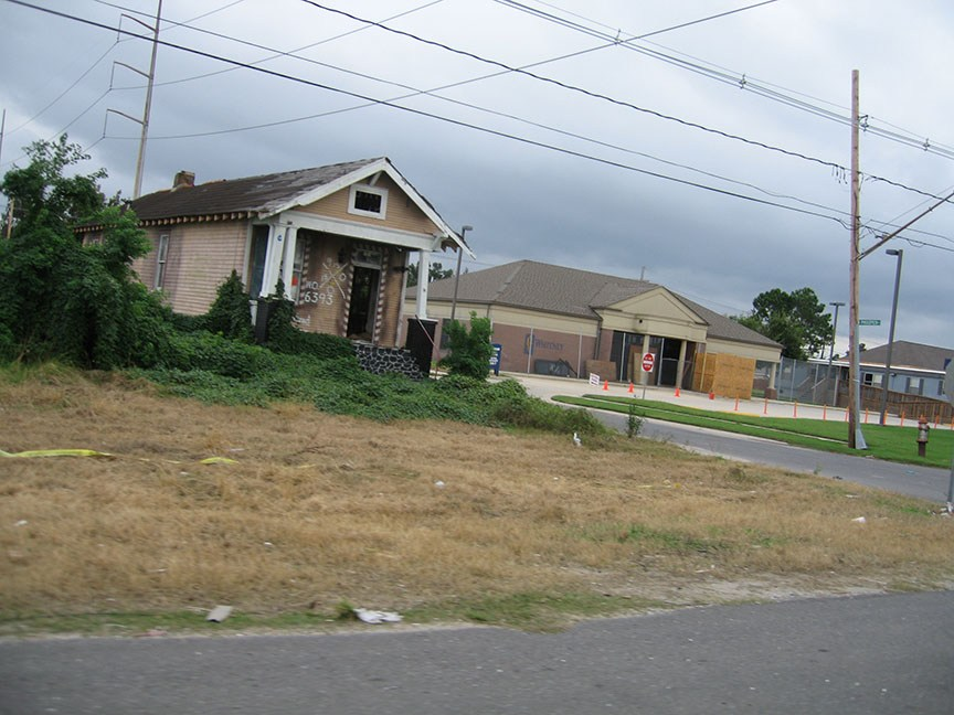 A house stands empty, without a door, covered in various agency markings, the path to the house has been overgrown; behind it a bank is boarded up