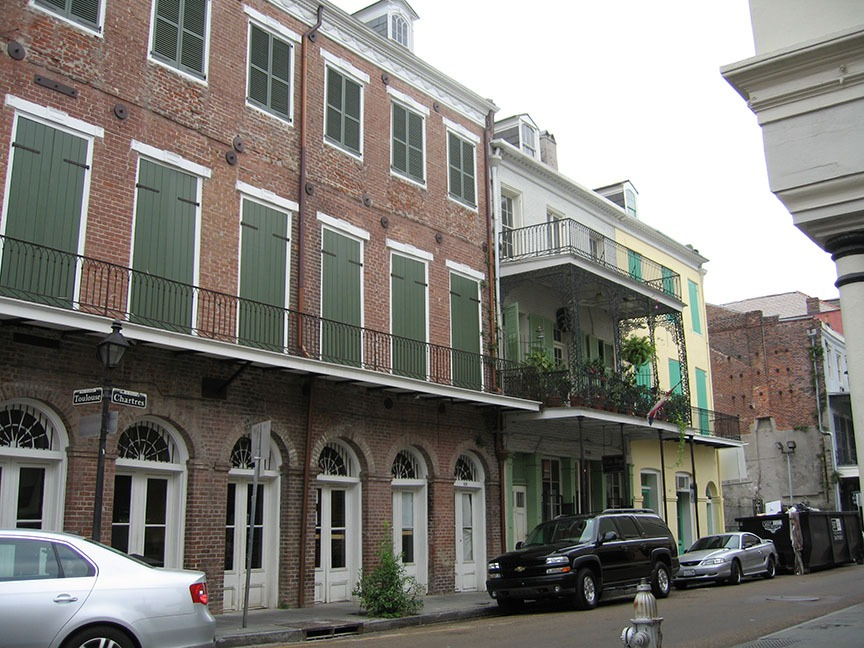"Brick buildings line the streets in New Orleans; street signs on the corner read ""Toulouse"" and ""Chartres"""