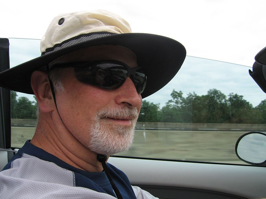 Rick Gifford primarily in profile, wearing a hat and a half smile on his face, drives a convertible with the top down