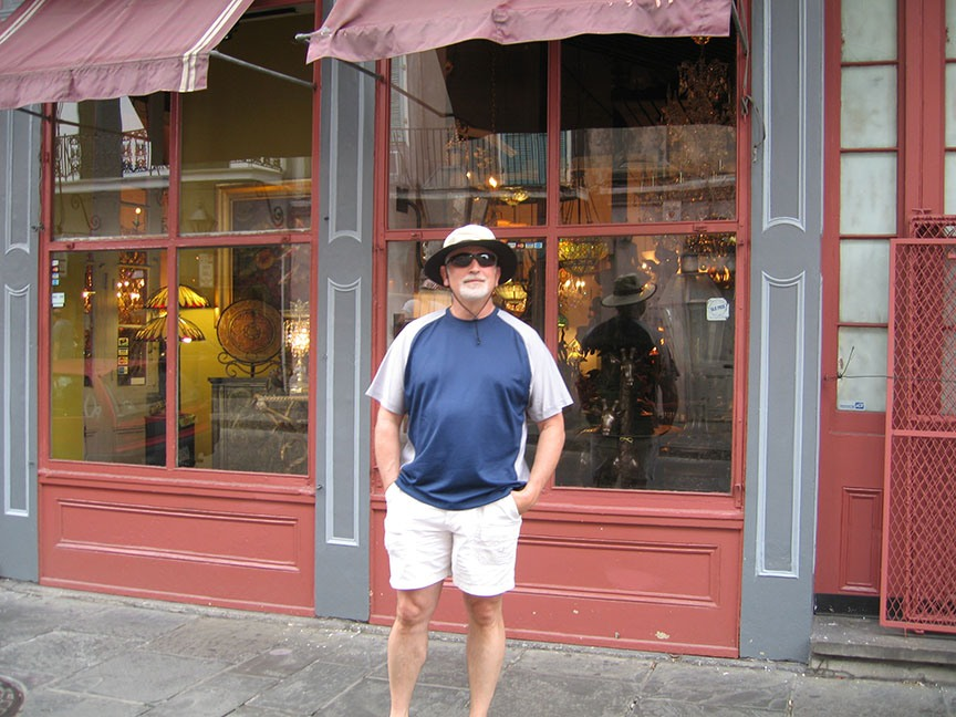 Rick Gifford stands in front of a shop with a red store front and offers a half smile to the camera.