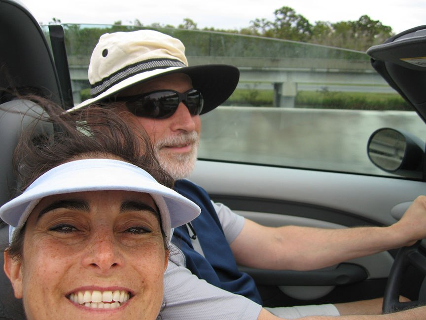 Lisa and Rick Gifford ride in a convertible with the top down, Lisa grins to the camera, Rick smiles while still watching the road.