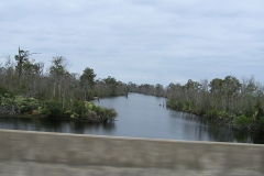 A waterway snakes out from beyond the edge of the highway; grey cloudy skies stretch out above it