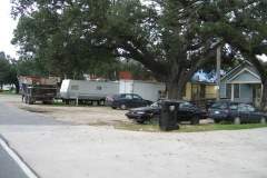 Houses line the street, white FEMA trailers stand in the front yard